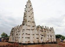 Garçon africain devant une mosquée d'argile en Afrique Photographie stock libre de droits