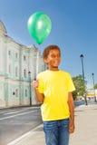 Garçon africain positif avec le ballon vert de vol Image stock