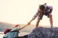 Garçon aidant une fille sur la montagne supérieure Photo libre de droits