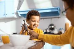 Garçon aimable d'aîné donnant à son frère un dinosaure de jouet Photos stock