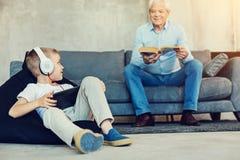 Garçon amical regardant son grand-père tout en jouant des jeux Image libre de droits