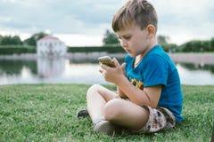 Garçon 5 années avec le téléphone intelligent se reposant sur l'herbe verte en parc Images libres de droits