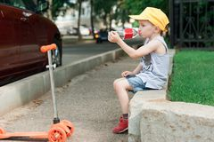Garçon 5 années, avec un scooter sur la route en parc L'enfant boit l'eau Vacances de famille Image libre de droits