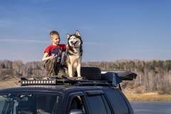 Gar?on 9 ans avec le chien enrou? se reposant sur la voiture de toit Amis sur la promenade dans le jour ensoleill? contre le ciel photographie stock