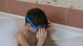 Garçon 6-7 ans se reposant dans le bain moussant et essayant de porter des lunettes banque de vidéos
