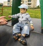 Garçon 1 3 ans se reposant sur la glissière d'un terrain de jeu dans le village Photo stock