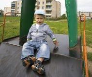 Garçon 1 3 ans se reposant sur la glissière d'un terrain de jeu dans le village Photos libres de droits