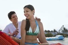 Garçon appliquant la lotion de protection solaire sur le dos de la fille Image libre de droits