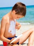 Garçon appliquant la protection solaire Photographie stock libre de droits