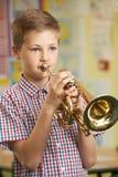Garçon apprenant à jouer la trompette dans la leçon de musique d'école photo stock
