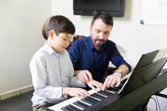 """Garçon apprenant à jouer le piano électrique conseils de S dans tuteur """" photo stock"""