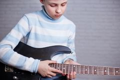 Garçon apprenant à jouer une guitare électrique Musique, passe-temps et leisur Photographie stock libre de droits
