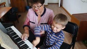 Garçon apprenant comment au piano de jeu banque de vidéos