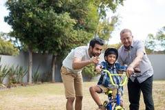 Garçon apprenant la bicyclette avec le père et le grand-père Photographie stock libre de droits