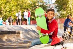 Garçon Arabe heureux avec la séance verte de planche à roulettes Photographie stock libre de droits