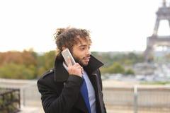 Garçon Arabe marchant près de Tour Eiffel avec le smartphone dans le MOIS lent Photographie stock libre de droits