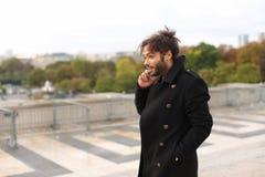 Garçon Arabe marchant près de Tour Eiffel avec le smartphone dans le MOIS lent Image stock