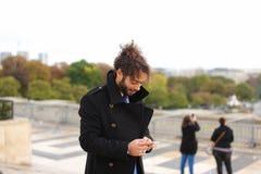 Garçon Arabe marchant près de Tour Eiffel avec le smartphone dans le MOIS lent Photographie stock