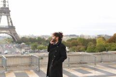 Garçon Arabe marchant près de Tour Eiffel avec le smartphone dans le MOIS lent Photo stock