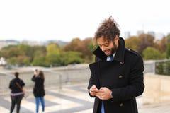 Garçon Arabe marchant près de Tour Eiffel avec le smartphone dans le MOIS lent Photos libres de droits