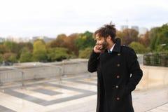 Garçon Arabe marchant près de Tour Eiffel avec le smartphone dans le MOIS lent Images stock