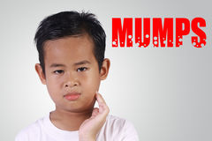 Garçon asiatique étant fatigué avec des oreillons image libre de droits
