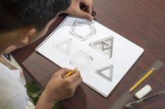 Garçon asiatique apprenant et pratiquant à dessiner les formes 3D sur le carnet de dessin sur le bureau brun à la maison Photo libre de droits