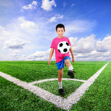 Garçon asiatique avec du ballon de football au terrain de football images stock