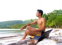 Garçon asiatique avec l'ordinateur portatif sur la plage Images libres de droits