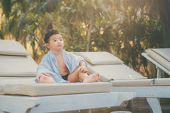 Garçon asiatique avec la serviette blanche se reposant sur une chaise ou un soleil de plate-forme de salon Images libres de droits
