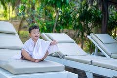 Garçon asiatique avec la serviette blanche se reposant sur une chaise ou un soleil de plate-forme de salon Photos stock