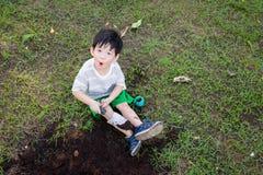 Garçon asiatique creusant dans le jardin images stock
