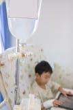 Garçon asiatique de maladie se trouvant sur le lit de malade dans l'hôpital Type de cru Image stock