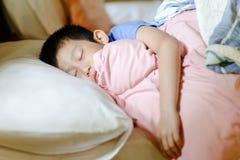 Garçon asiatique de sommeil sur le lit Image stock