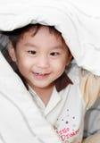Garçon asiatique de sourire couvert par la couverture Photographie stock