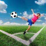 Garçon asiatique de tache floue de mouvement avec du ballon de football au football photographie stock