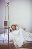 Garçon asiatique dormant sur le lit de malade avec l'intravenous IV de pompe d'infusion Photos libres de droits