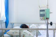 Garçon asiatique dormant sur le lit de malade avec l'intravenous IV de pompe d'infusion Photos stock