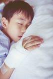 Garçon asiatique dormant sur le lit de malade, intravenous salin (iv) en main Photographie stock libre de droits