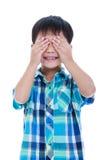 Garçon asiatique espiègle couvrant son oeil D'isolement sur le fond blanc Photographie stock libre de droits