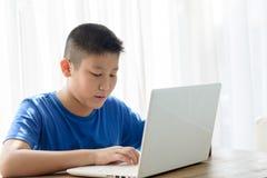 Garçon asiatique heureux à l'aide du comprimé à la maison Photos stock