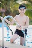Garçon asiatique heureux dans le maillot de bain montant la piscine image libre de droits