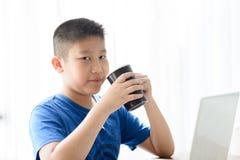 Garçon asiatique heureux tenant la tasse noire images libres de droits