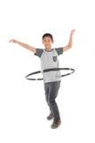 Garçon asiatique jouant avec le hulahoop sur un blanc Image libre de droits