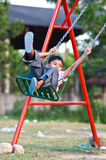 Garçon asiatique jouant l'oscillation à la cour de jeu Photo stock