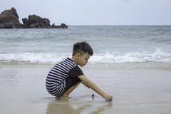 Gar?on asiatique jouant le jouet sur une plage de mer images libres de droits