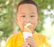 Garçon asiatique mangeant la crème glacée en été Photo stock