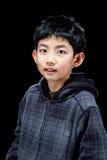 Garçon asiatique mignon posant sur le fond noir dans le studio images libres de droits