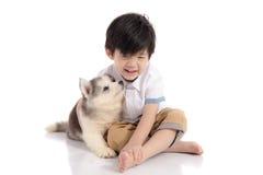 Garçon asiatique mignon s'asseyant avec le chiot de chien de traîneau sibérien photos stock