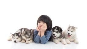 Garçon asiatique mignon se trouvant avec des chiots de chien de traîneau sibérien Photo libre de droits